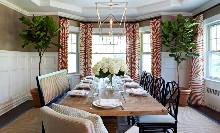 The formal dining room has a lot of traditional features that are livened up by the bold and unexpected orange zebra patterned curtains. The right side of the table has more traditional, formal dining chairs, while the left has a casual bench. At the head of the table is a cushioned dining chair.