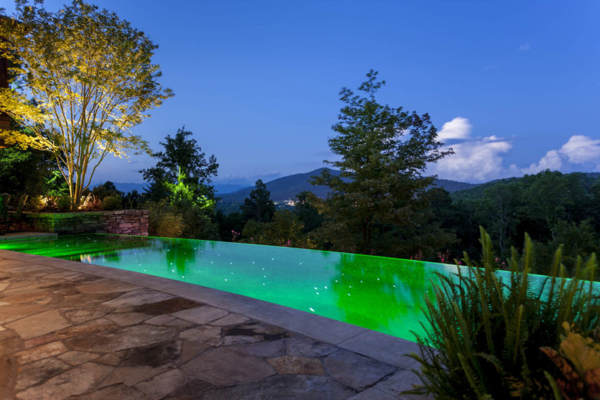 The infinity pool, lit green from within at dusk, adds a striking centerpiece to the mountainside patio area.