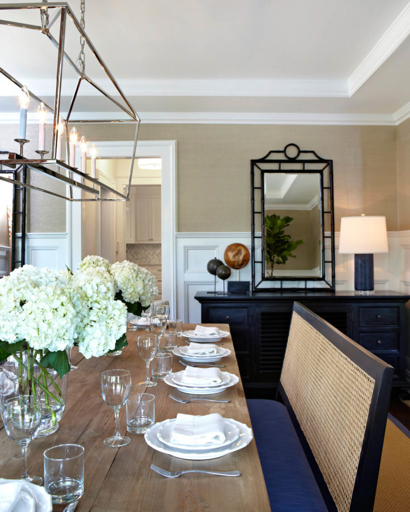 The length of the light fixture doesn't effect the dainty construction of the piece. On the rear wall of the room, near the entrance, is a dark wood buffet table.