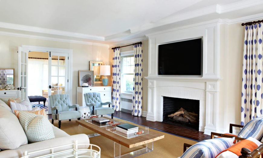 The spacious living room is in more subtle colors than the dining room. The blues are more on the muted side in various patterns including stripes and polkadots. The open hearth wood-burning fireplace has a brick hearth and is topped by a wall-mounted television.
