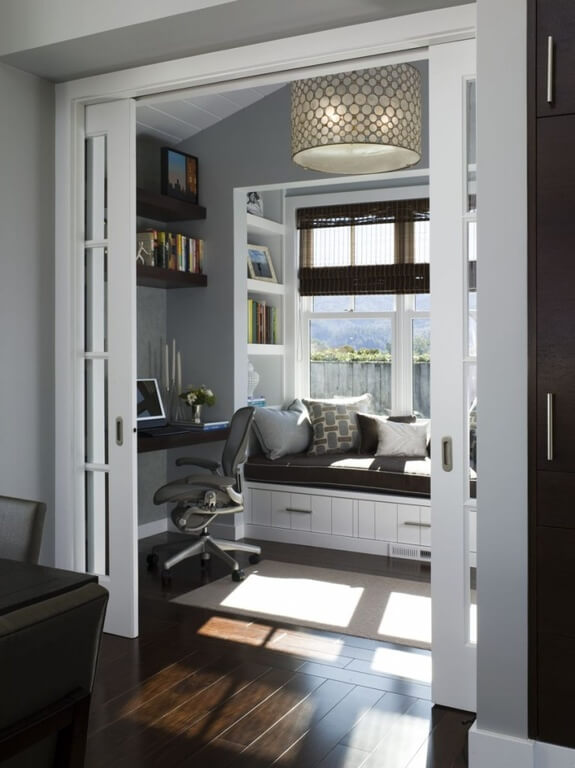 Standing past a set of white wood and glass pocket doors, this cozy study features a broad cushioned window seat over white cupboard storage. Built-in shelving and writing desk add function and save space.