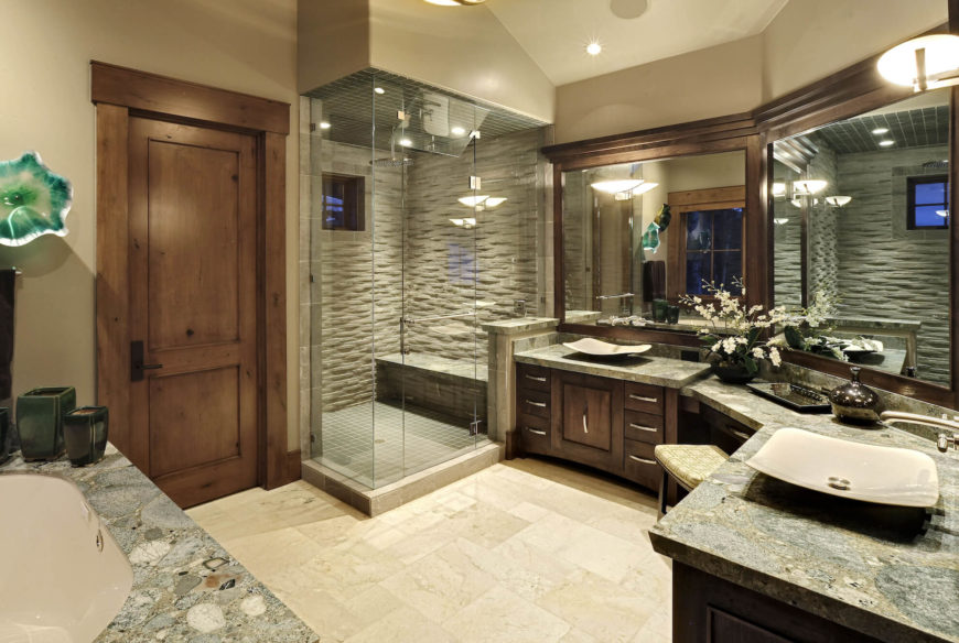 The lavish master bathroom features a wraparound double vanity with vessel sinks over marble countertops and dark wood cabinetry. Large format mirrors and a glass enclosed shower add a bright and open sense.