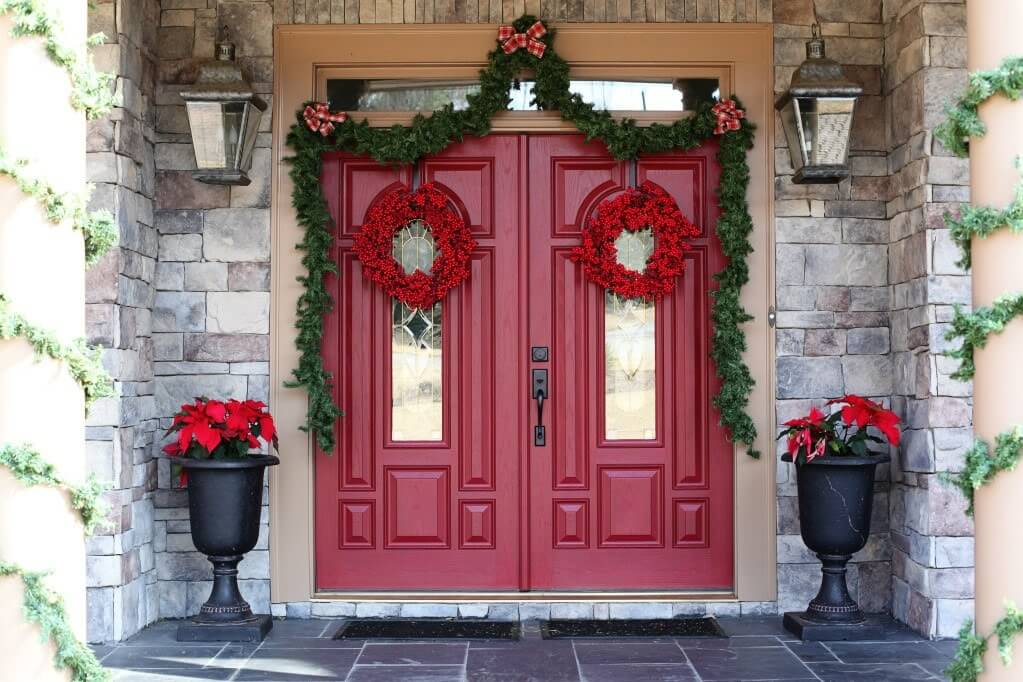 This impressive stacked-stone home is decorated for the holidays, with two black urns playing host to a pair of poinsettia plants. The double doors of the entryway are decorated with a swag of pine garland and holly wreathes. The pillars on either side of the stairs are also decorated with pine garlands.