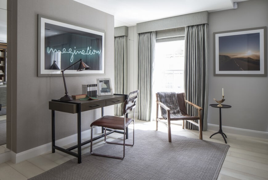 """In this thoroughly modern, neutral grey toned open space, an office is created by the large area rug centering a dark wood and metal writing desk and natural wood framed slingback chair near the full height window. The muted palette is punctured by the """"imagination"""" neon art piece on a wall flanked by vertical mirror panels."""