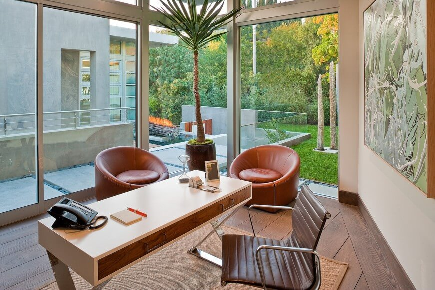 This brightly sunlit, ultra-modern home office stands in the corner of a home with full height exterior glass and extensive water features. Natural hardwood flooring contrasts with minimalist desk design and pair of circular club chairs in rich leather.