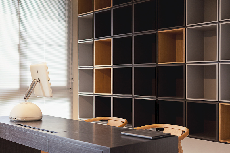 In a sleekly modern space using an extensive variety of wood tones, a wall-size cubic shelving system stands over a dark stained wood reading desk, contrasting with a pair of natural wood toned chairs.