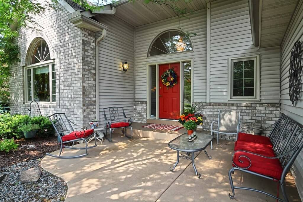 This brick house has a bold red door in a more simple design. Seamless sidelights run the length of the door and are topped by an arched transom. The front walkway includes a small patio just beneath the single step. The absence of a porch is made up for by this seating arrangement.