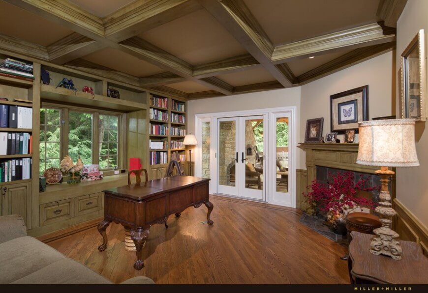 This large natural wood filled study sprawls out beneath a cross-beam ceiling, with a large ornate executive desk at center. Stone wrapped fireplace sits in one corner, while full height bookshelf wall frames a trio of windows on the opposite end.