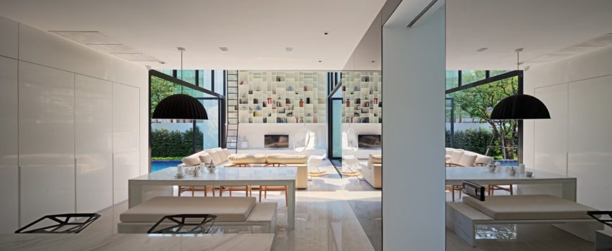 The large, open design living room area houses an immense, two story bookshelf against the far wall, surrounded by bespoke white modern furniture.