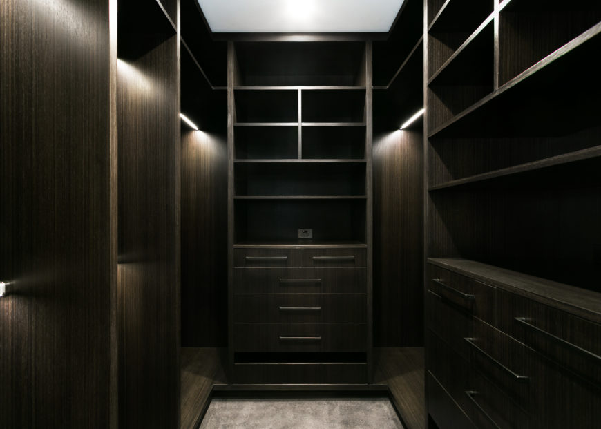 The dark stained timber walk-in closet hosts an array of storage options in various configurations. Inner lighting and minimalist hardware complete the bespoke design.