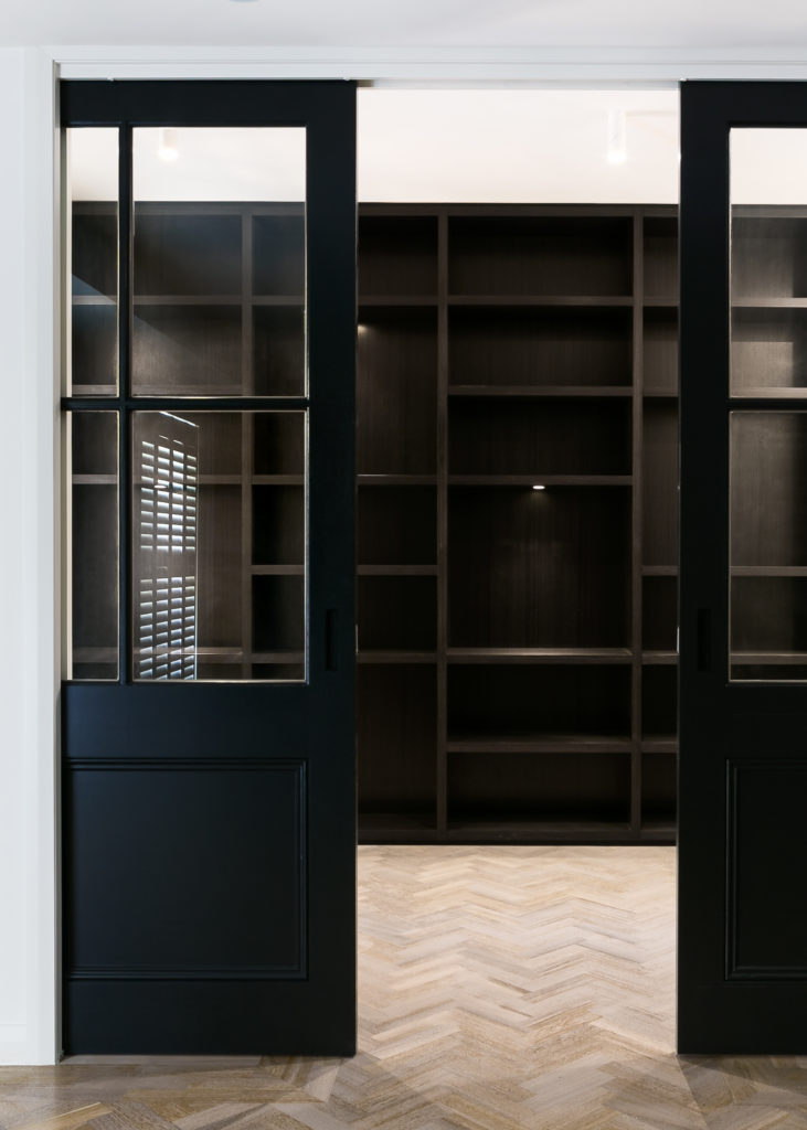 Here's another elaborate storage space, outside the main open area of the home. A pair of window-equipped pocket doors in dark timber open to reveal shelving mirroring that in the master walk-in closet.
