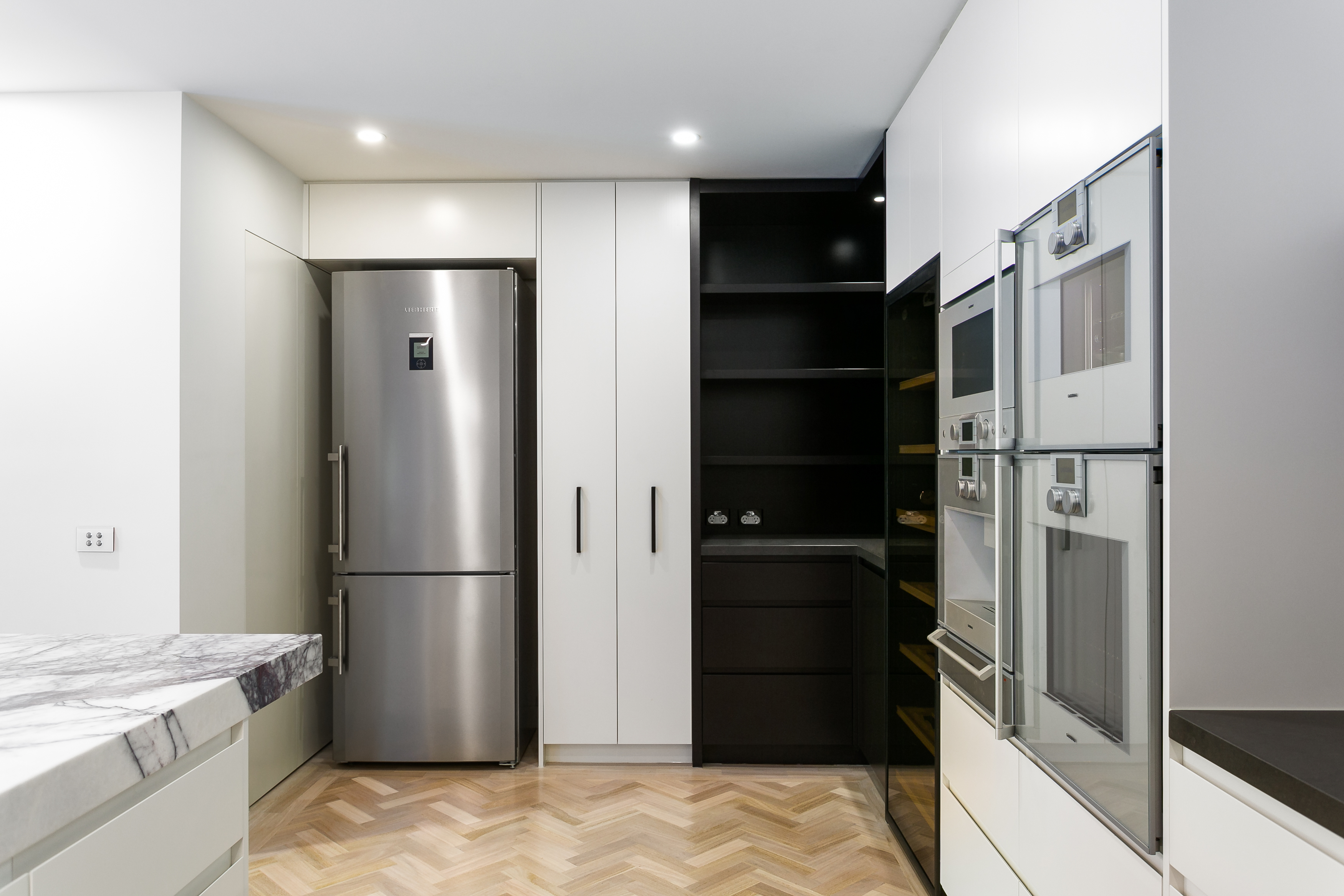 Highlighted with stainless steel appliances and dark wood corner shelving, the kitchen also hosts a full height built-in wine rack with glass door.