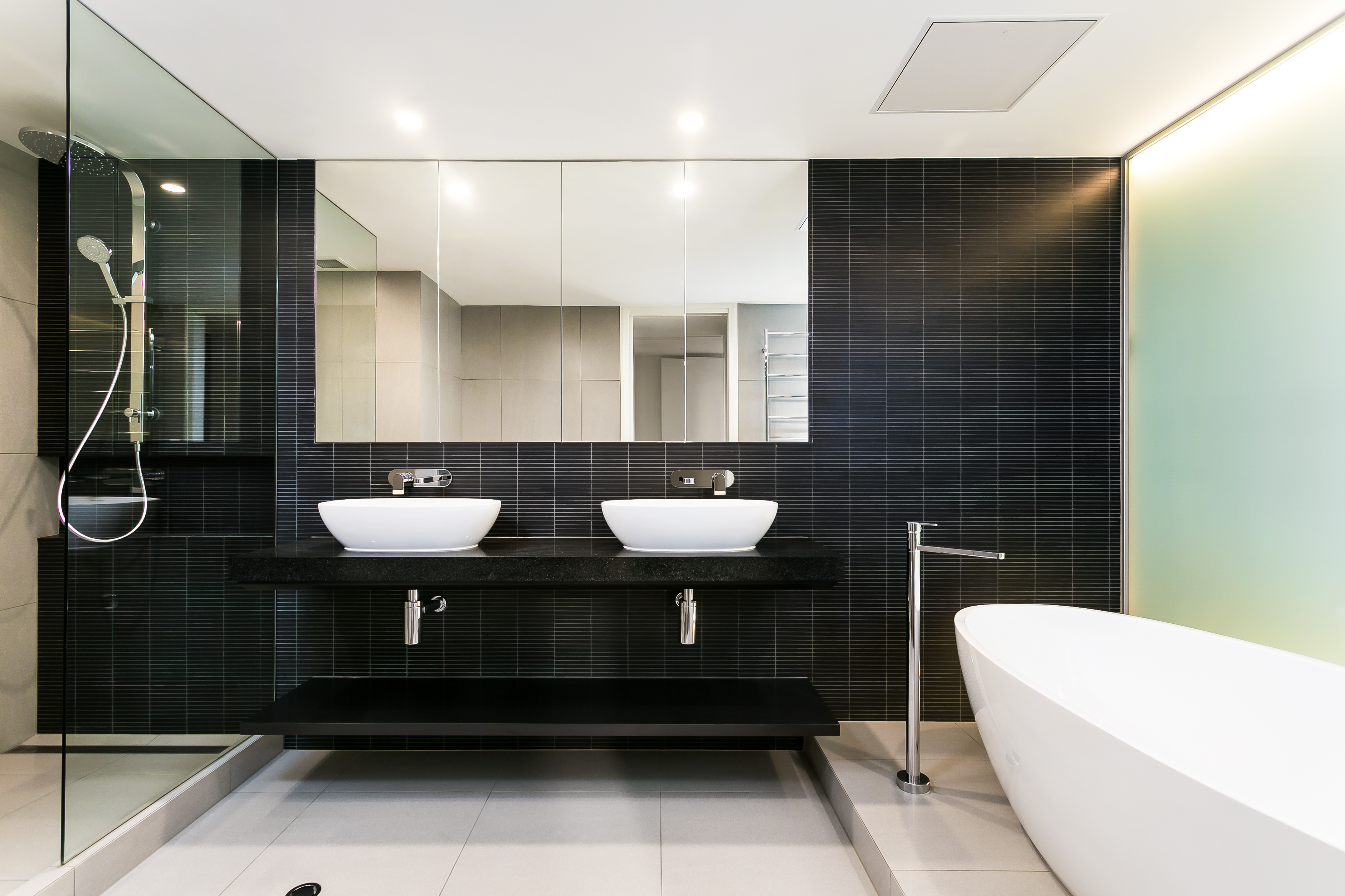 The master bath hosts a high contrast mixture of tones, with black tiled wall over off-white large format beige floor tiling, plus white pedestal tub and vessel sinks. The floating black vanity hangs next to a large glass enclosed shower.