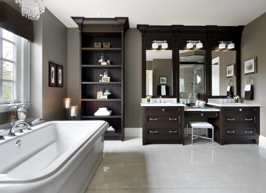 This master bathroom features a freestanding shelf along with a powder desk in between two sinks. The deep soaking tub is lighted by a gorgeous chandelier.