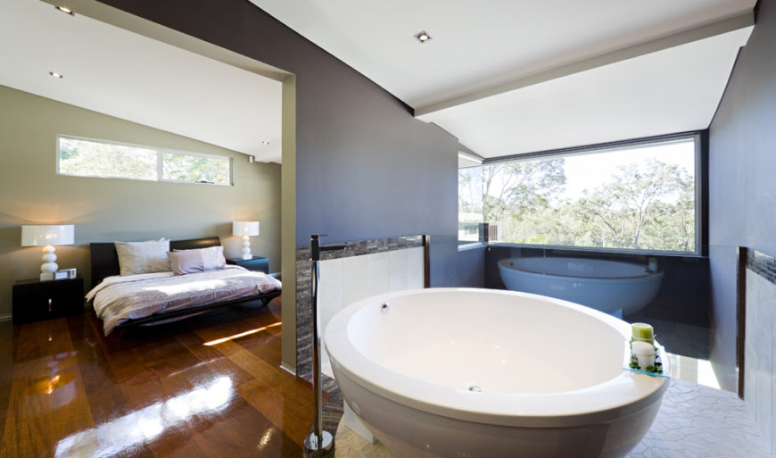 The master bedroom en suite floats above the open living room, with only a glass panel separating the space. A large circular pedestal tub stands at center, surrounded by organic textured white tile.