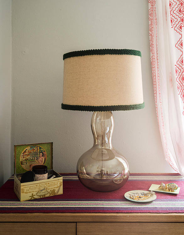 The dresser holds unique details, including this blown glass frame lamp with green-trimmed shade.