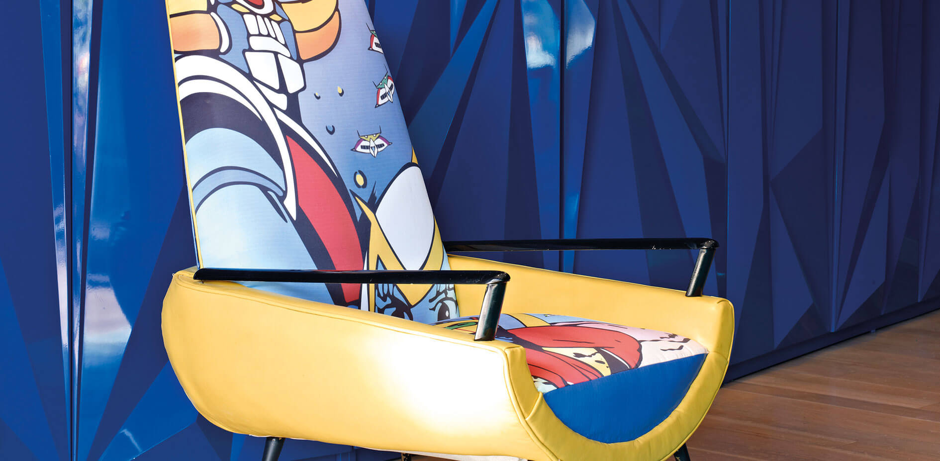A close up of the colorful and unique chair. The style is futuristic, and the bold yellow contrasts with the angular pattern on the blue walls behind it.