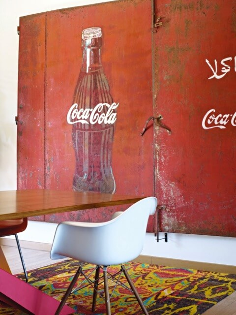 On the wall left of the table is a large, repurposed Coca-Cola memorabilia, now serving as large wall art. The rug beneath the dining room table, like the living room rug, is brightly colored and patterned.