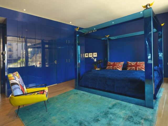 The master bedroom is boldly colored in blue. The walls are a glossy, deep blue with storage all along the left wall. The four-post bed is in metallic blue, with velvet bedding and two Union-Jack pillows. An aqua rug and a brightly colored chair add a bit of color variety.