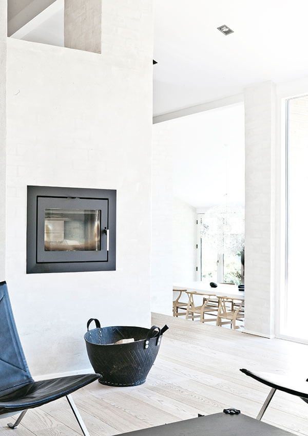 The singular, subtle fireplaces are framed in black for utmost contrast, meshing with the dark furniture tones in an otherwise bright space. From here, we see all the way to the opposite corner of the home.