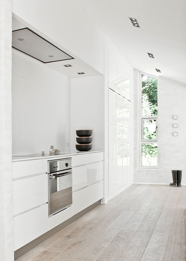 Full height white minimalist cabinetry stands beside the kitchen, connecting to an external wall housing a trio of windows that reach to the sloped ceiling.