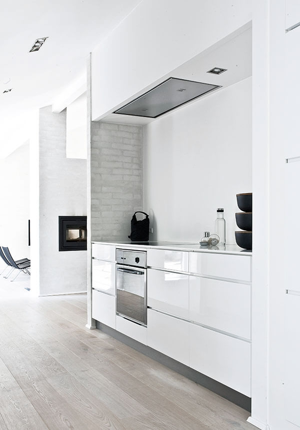 Glossy white cabinetry pairs with stainless steel appliances for a high contrast, modern look.