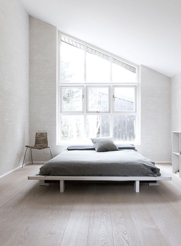 Master bedroom evokes the vertical windows of the main body of the home, widened to accommodate the entire space. A platform bed holds the center, flanked by an accent chair and white cubic shelving.