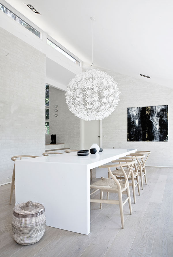The expansive dining room level holds this lengthy single-piece white slab table, paired with a set of wicker seat, light natural wood chairs. A single dark painting on the far wall contrasts with the lighter tones.