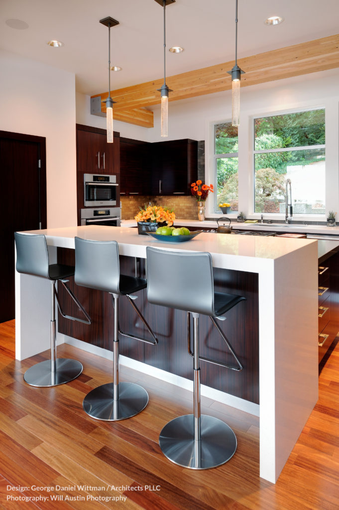 Moving into the kitchen space, we have a bold, two tier island with minimalist white dining area and lower cooktop space. Modern look stainless steel bar stools providing seating beneath a trio of slim pendant lights.