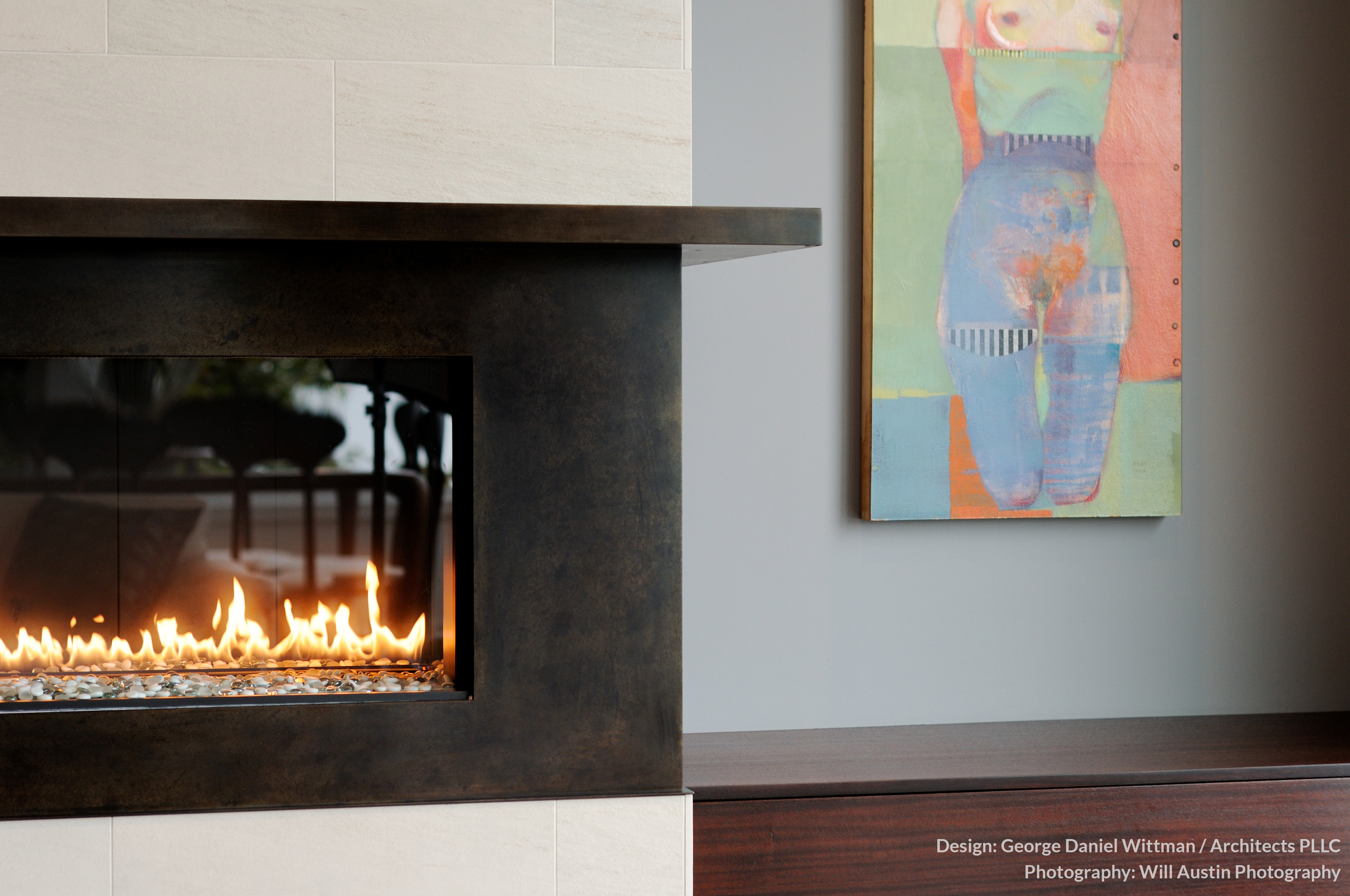 The fireplace, framed in dark metal between layers of white stone, stands in contrast with the soft hues of the wall. An art piece seen in this room exemplifies the style of the home, with striking imagery punctuating a neutral palette.