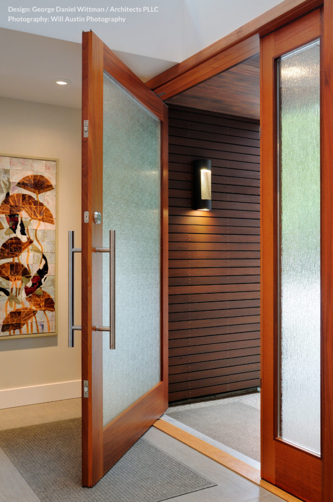The main entryway features a large door with art glass set into a walnut frame for a bold, warm look as one enters the home.