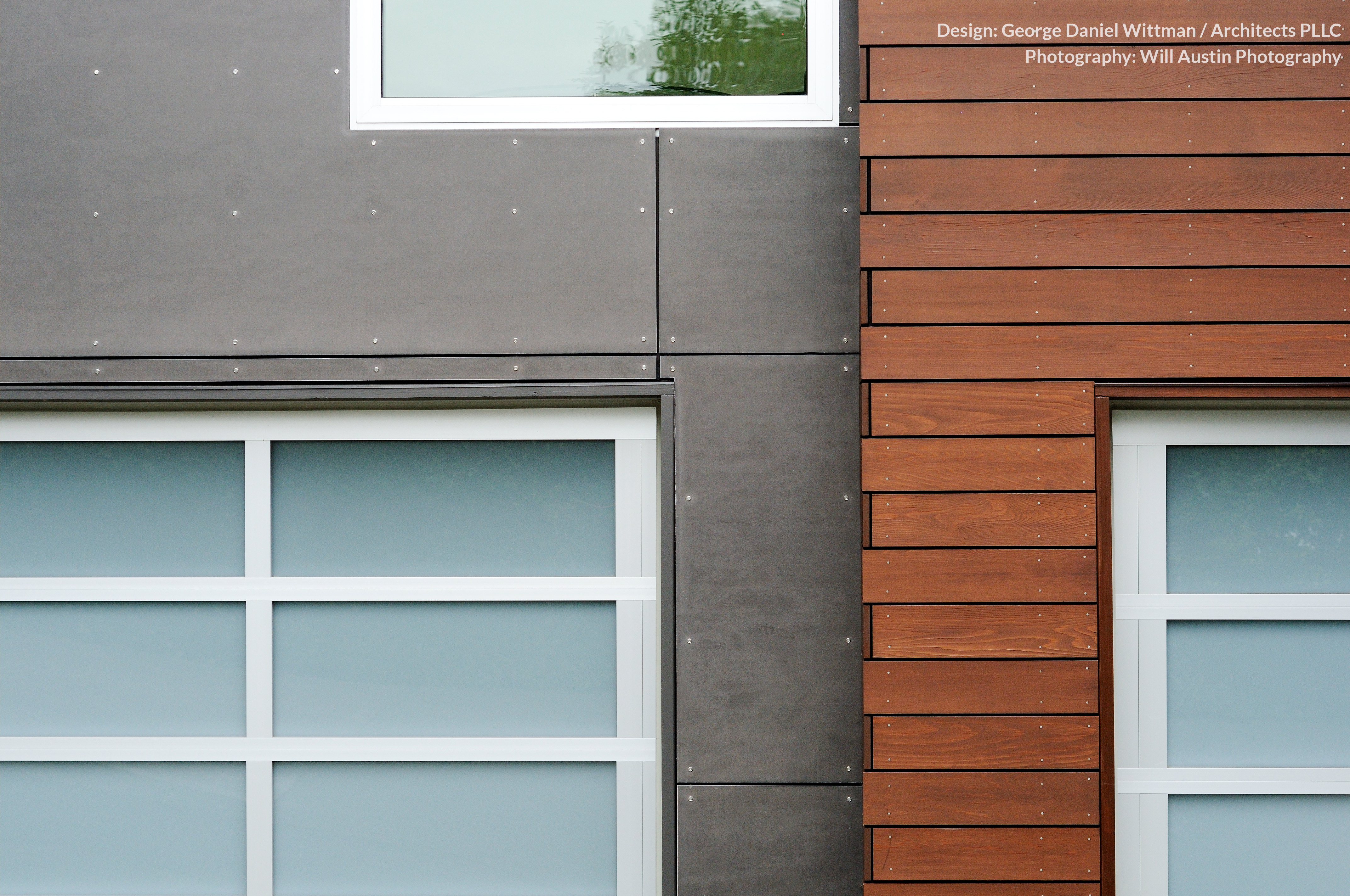 This shot of the exterior highlights the point at which cedar planks meet the cement board panels. The glass and metal garage doors can be seen here.