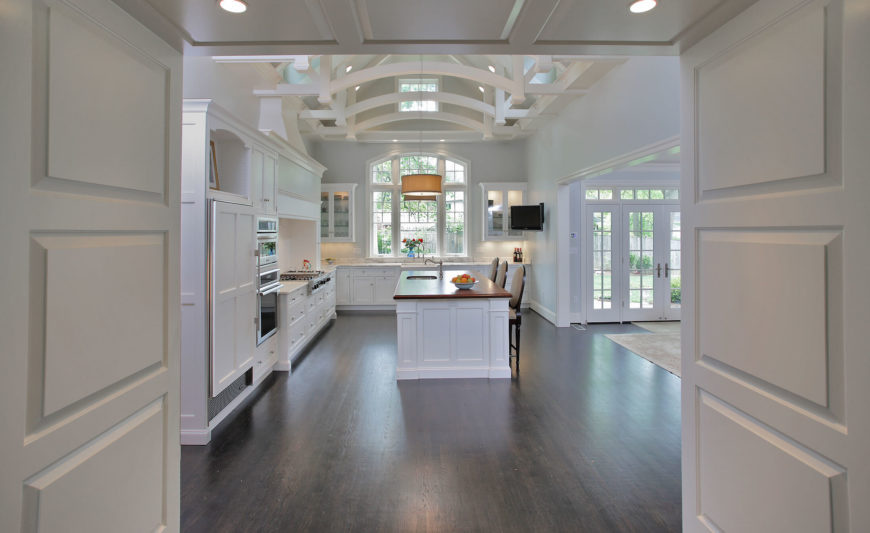 Viewing The Kitchen Through An Entry Hall, We See A Wide Swath Of Dark  Hardwood