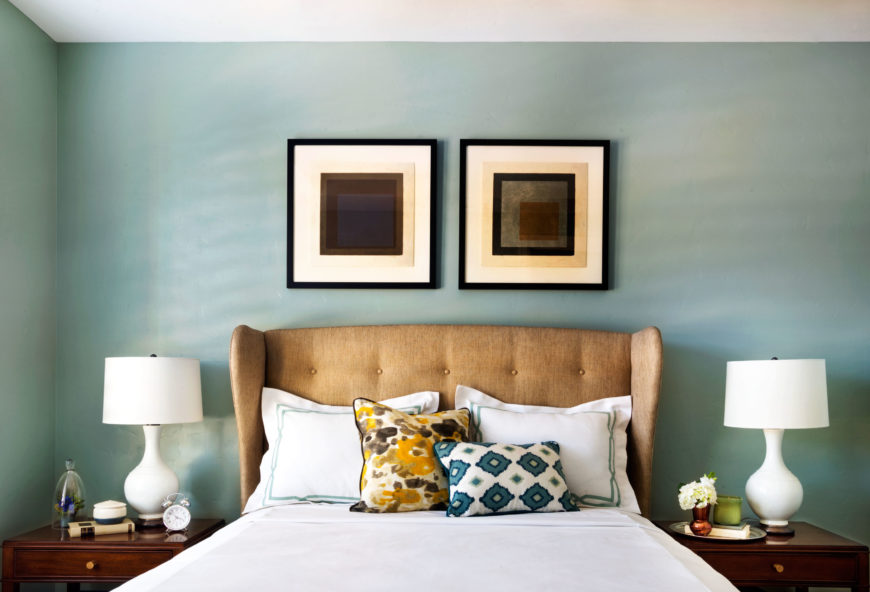 Upstairs, the guest bedroom has white bedding with blue and yellow accents. Matching night stands with white curvy lamps sit on either side of the upholstered headboard.