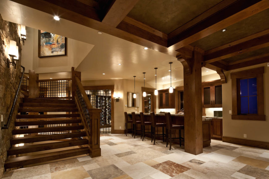 Beside the central all-wood staircase wrapping the stone structure, we see this unique wine bar space, replete with granite topped island and bar stool seating. The extensive wine cellar can be see through doorway to the left.