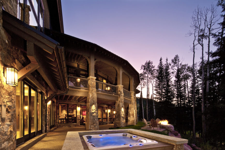 On the back side of the home, we see a private patio with jacuzzi, as well as a hillside fire pit area, overlooked by the wraparound balcony and large stone pillars surrounding the home. Full height windows throughout allow for the interplay of indoor and outdoor elements.