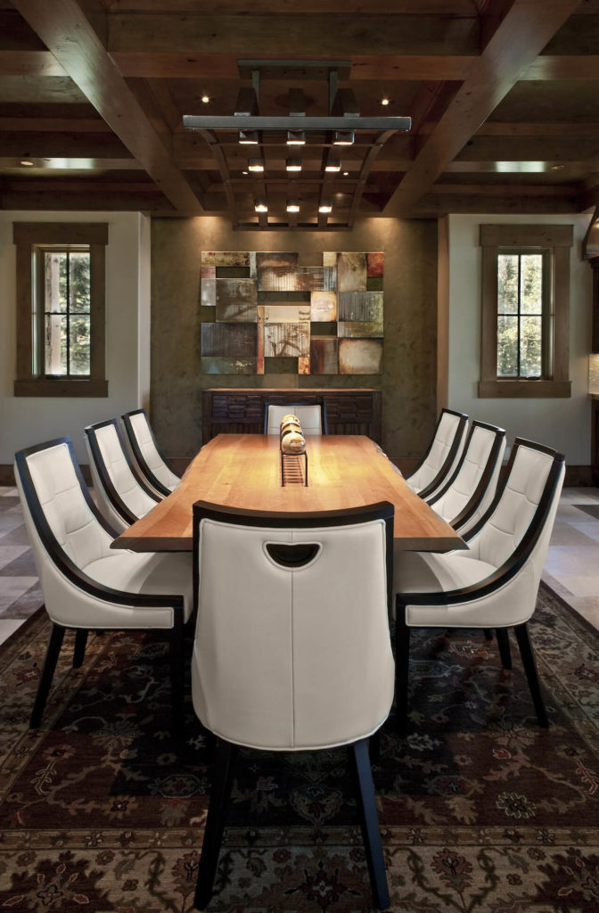 The dining room features a unique arched lighting feature below its lattice-like wood beam ceiling. The table is a single slab of natural wood, surrounded by modern styled Parson chairs, mixing the contemporary and rustic elements.