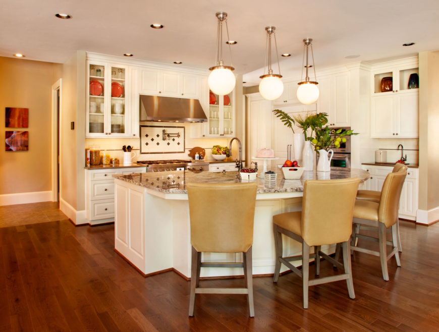 The eat-in kitchen is built for entertaining. The large kitchen island curves out into a bar area with three globe lights above it. The pristine white cabinetry and light marble countertops contrast with the rich tones of the hardwood flooring.