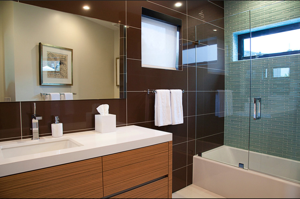 A second bathroom features a more lively mixture of tones, with aqua hued tile in the glass wrapped shower, light wood vanity cabinets, and dark large format wall tiling.