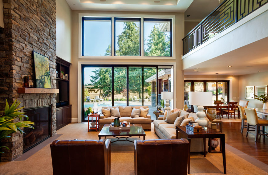The foyer leads through a small hallway to the open-concept living area, which includes the living room, kitchen, and dining room. The soaring ceiling of the living room is open to the upstairs hallway. The large rustic stone fireplace is nearly as wide as the sofa directly across from it. Glass doors can be used to lead directly outside to the pool.