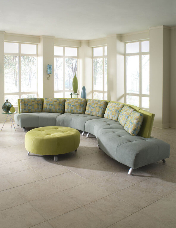 Overstuffed, button tufted cushioning wraps a solid wood frame on this colorful sectional, curved into an almost S-shaped frame. Large green ottoman matches the backing material, while multicolored pillows provide comfort.