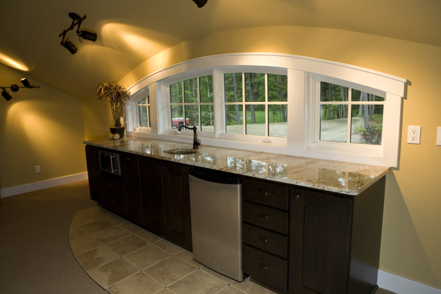 The family room houses this compact kitchenette, with granite countertop over dark wood cabinetry and sink below an array of arched windows.