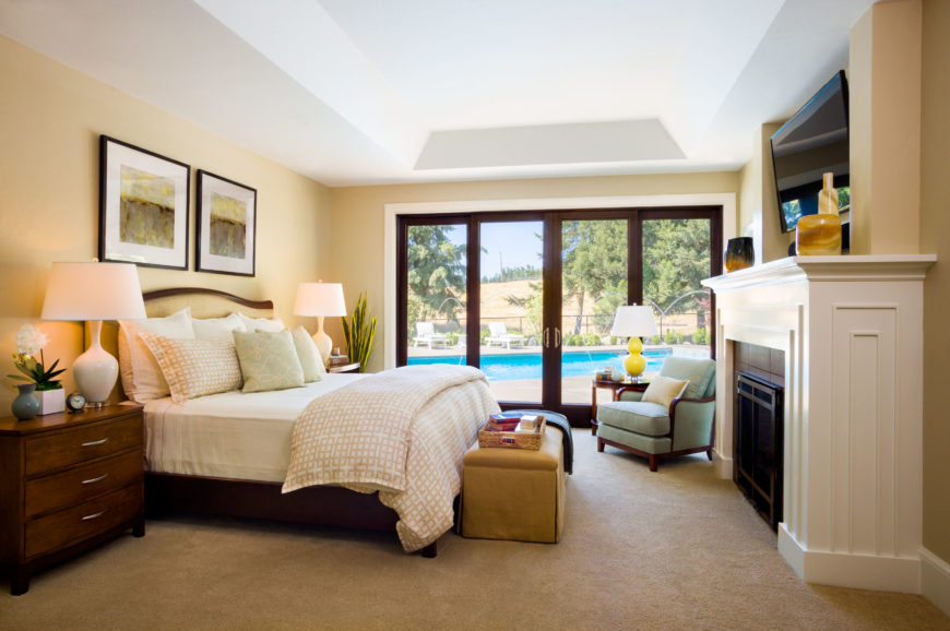 The master suite is located on the ground floor, with French doors that lead out to the backyard pool. The large fireplace has a white mantle with wainscoting details. Set into the wall is the wall-mounted television.