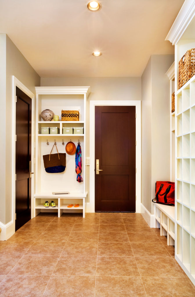 The more casual entrance is the mudroom, which has warm mottled tile that hides a little bit of dirt and white storage cubbies in addition to the coat closet.