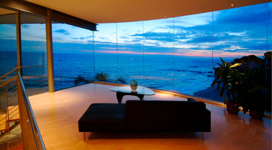 Sunsets are a major attraction for a home wrapped in glass. This living room with black chaise and glass top coffee table stands above over more of the hardwood flooring.