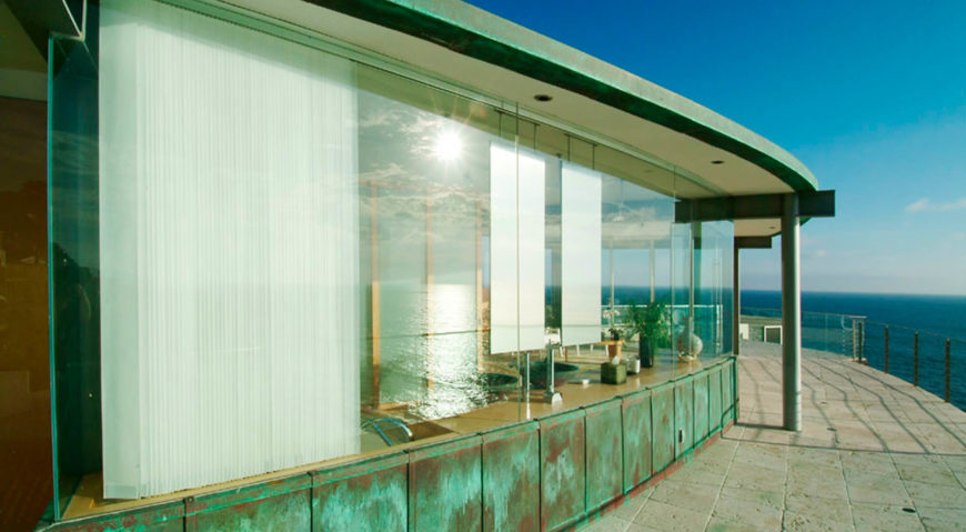 On the upper level stone balcony wrapping the ocean side of the home, we see the gentle curve of the structure, sandwiching the large format glass panels between layers of exposed structure.