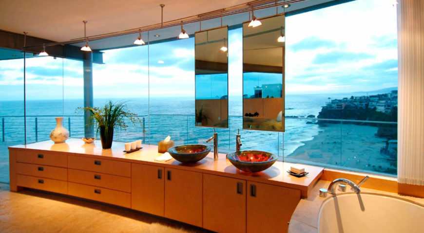 The master bathroom hangs a pair of vanity mirrors in front of the expansive exterior glass, over a natural wood countertop. Large soaking tub at right enjoys the ocean views or can be made private via full height curtains.