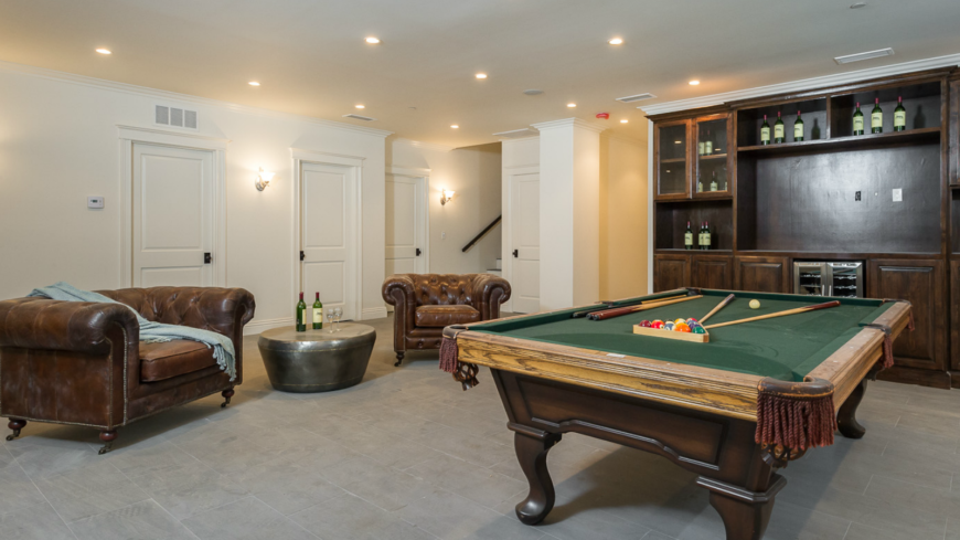 The billiards room is in light taupe tile and white walls with small pot lights dotting the ceiling. The large built-in shelving contains a small refrigerator and a bar. Two large, deep leather chairs have a metallic side table between them.