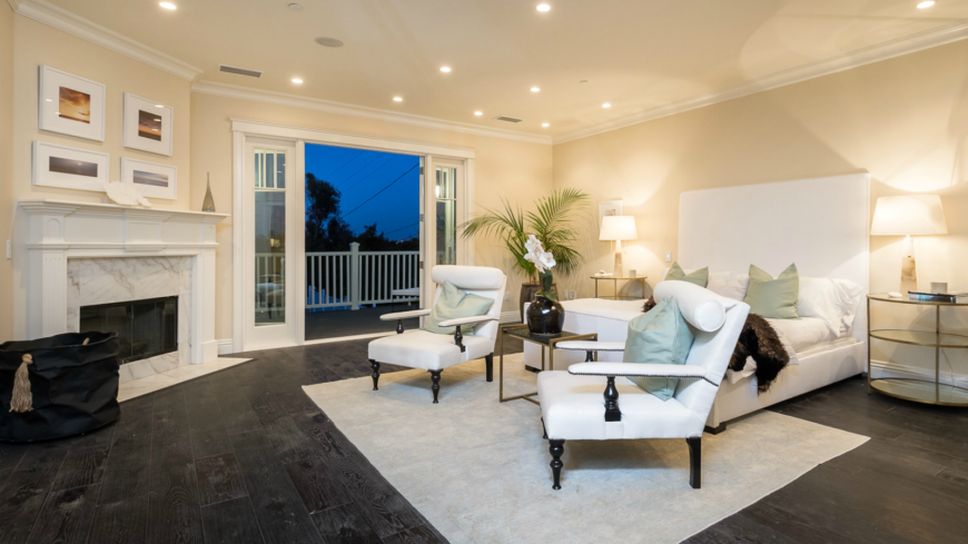 The spacious master bedroom on the second level has a beautiful enclosed fireplace in marble and wood, topped by four sunset pictures. The white bed frame has an enormously tall headboard and is flanked by two white chairs. Glass doors lead to the balcony overlooking the backyard.