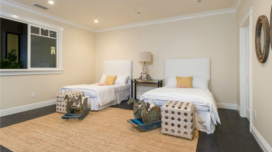 The kid's bedroom is similarly designed to the sitting room. They have the same color palette, accent pillows, and natural fiber rug that covers the dark hardwood flooring. Antique swan rockers sit next to wicker storage cubes at the foot of each bed.